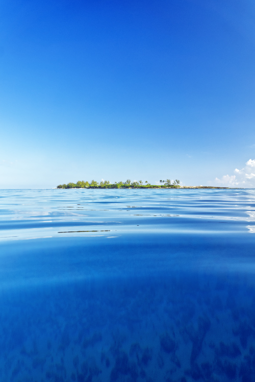 Island near blue ocean at sunrise